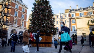 Pedestrians wearing masks pass a Christmas tree in Covent Garden in central London on November 22, during England's four-week national lockdown. (TOLGA AKMEN/AFP/Getty Images)