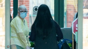 A nurse in protective gear greets a woman entering the Seven Oaks Long-Term Care Home in Toronto on Thursday, April 2, 2020. THE CANADIAN PRESS/Frank Gunn