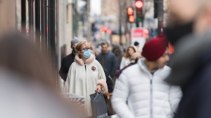 People wear face masks as they walk along a street in Montreal, Sunday, November 29, 2020, as the COVID-19 pandemic continues in Canada and around the world. THE CANADIAN PRESS/Graham Hughes