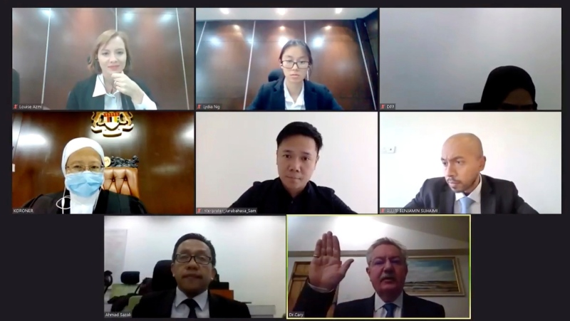 In this image from video released by Malaysian Judiciary, Nathaniel Cary, a forensic pathologist, bottom right, raises his hand to take his oath ahead of his testimony being provided online from the United Kingdom during a Malaysian virtual inquest on Monday, Nov. 30, 2020. (Malaysian Judiciary via AP)