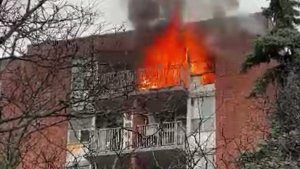 Flames are seen shooting from an apartment unit on the seventh floor of a building at 100 Cavell Avenue in Etobicoke on Nov. 30, 2020.