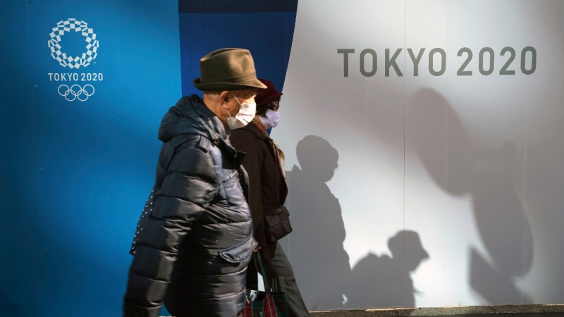 A man and a woman wearing protective masks to help curb the spread of COVID-19 walk in front of logos of Tokyo 2020 Olympics, on Nov. 30, 2020. (Eugene Hoshiko / AP)
