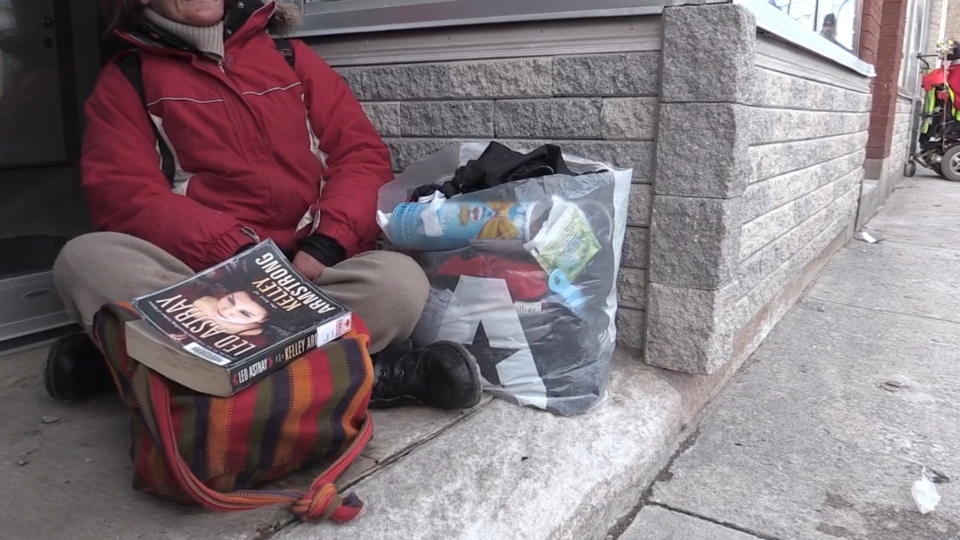 A person living with homelessness sits in a doorway in London, Ont.