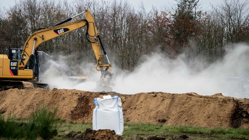 A bag of calcium oxide is seen in the foreground as an excavator buries dead mink in ditches in a military area near Holstebro, Denmark on Nov. 9, 2020. (Morten Stricker/Ritzau Scanpix/AFP/Getty Images/CNN)