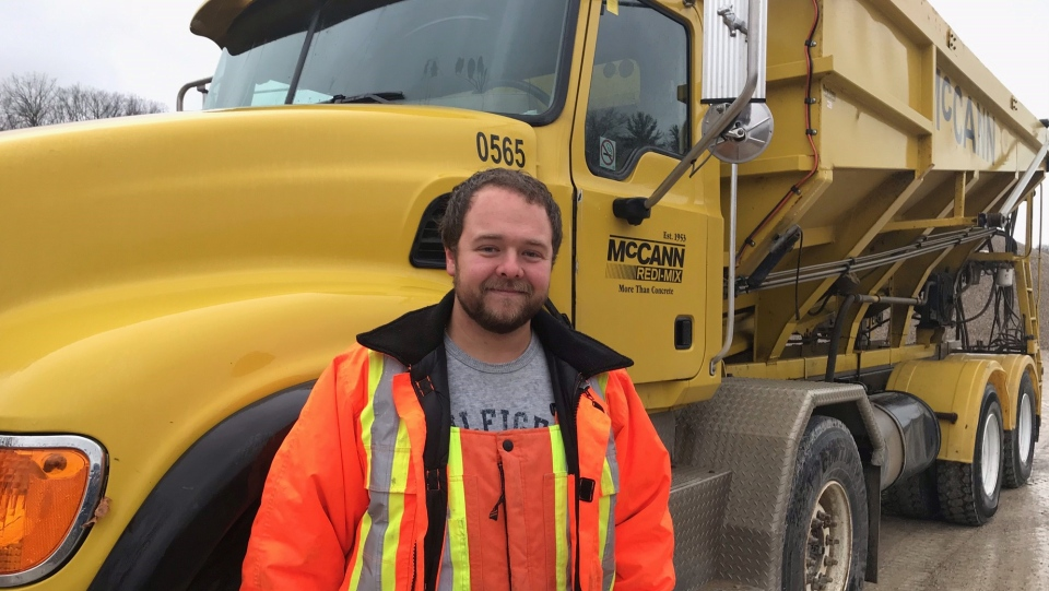 Jake Johnson of Exeter, Ont. stands by a dump truck on Monday, Nov. 30, 2020. The truck was used to save the life of a woman trapped in a burning car in Middlesex County and Johnson has been awarded a community commendation. (Sean Irvine / CTV News)