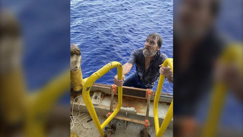 Stuart Bee, 62, climbs aboard the Coast Guard motor vessel Angeles. (US Coast Guard via CNN)