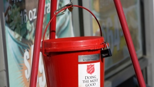 "The iconic Salvation Army donations collections bucket swings outside a Corner Market grocery store in Jackson, Miss., Wednesday, Nov. 25, 2020, as a bell ringer, unseen, wishes customers a ""Happy Thanksgiving,"" while non-vocally soliciting for donations. (AP Photo/Rogelio V. Solis)"