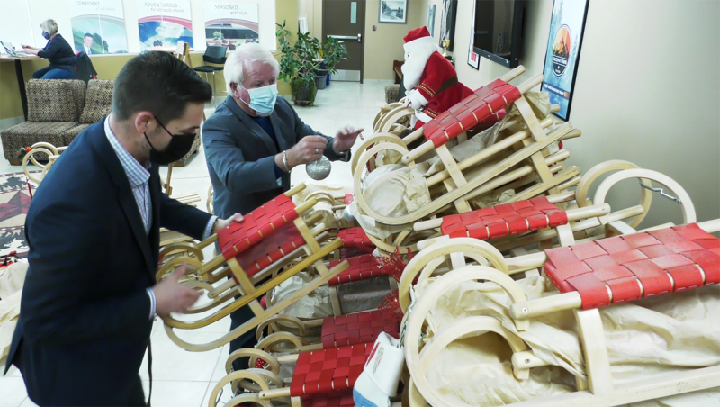Cochrane Toyota general manager Ryan Baum and former Stampede Wrestling star Dan Crawford inspect a shipment of Gloco handmade German sleds, which are being distributed to Calgary children over the holidays
