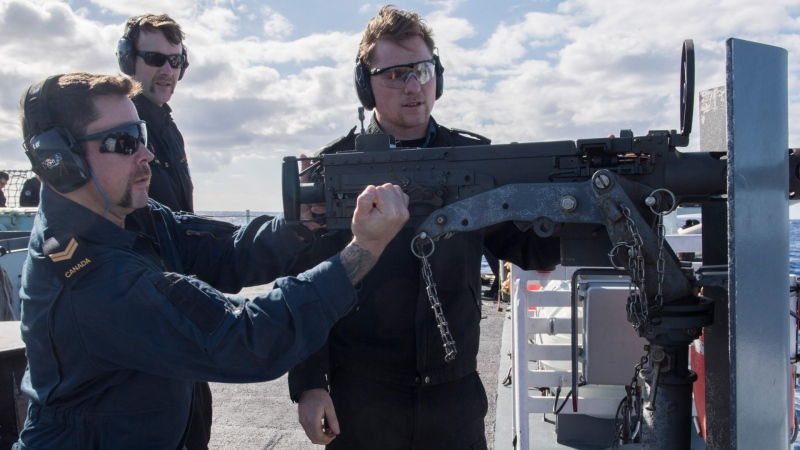 Sailor Christopher Albin prepares to fire the .50 calibre machine gun during a weapons practice onboard HMCS Calgary in the Pacific Ocean on December 4, 2018. (Mike Goluboff, MARPAC Imaging Services)