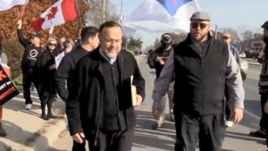 Herbert Hildebrant (R ) walks alongside his father Henry Hildebrant at the Freedom March in Aylmer, Ont. Nov 7, 2020.