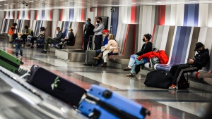 People wait for their baggage at Boston Logan International Airport in Boston on Nov. 25, 2020. (Erin Clark/The Boston Globe/Getty Images)