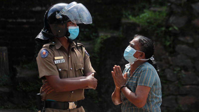 A family member of an inmate pleads to a policeman as she seeks information on the condition of her relative outside the Mahara prison complex following an overnight unrest in Mahara, outskirts of Colombo, Sri Lanka, Monday, Nov. 30, 2020. (AP Photo/Eranga Jayawardena)