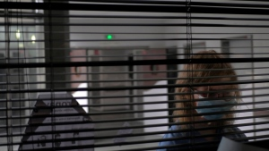 A patient looks through metal shutters in the Rouvray psychiatric hospital, in Rouen, western France, Wednesday, Nov. 25, 2020. (AP Photo/Thibault Camus)