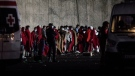 Migrants stand at Arguineguin port after their rescue on the southwestern coast of the Gran Canaria island, Spain on Tuesday, Dec. 1, 2020. Emergency services in Spain's Canary Islands say that 68 northern Africans have been the first migrants to arrive in the archipelago since authorities dismantled a makeshift camp that had brought criticism and shame to authorities. (AP Photo/Javier Fergo)