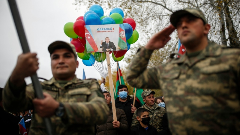 Azerbaijani soldiers and civilians hold a portrait of Azerbaijani President Ilham Aliyev that reads 'Karabakh is Azerbaijan!' as they celebrate the transfer of the Lachin region to Azerbaijan's control in Aghjabadi, Azerbaijan, on Dec. 1, 2020. (Emrah Gurel / AP)
