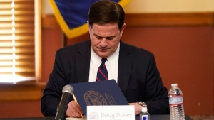 Arizona Gov. Doug Ducey signs election documents to certify the election results for federal, statewide, and legislative offices and statewide ballot measures at the official canvass at the Arizona Capitol, on Nov. 30, 2020. (Ross D. Franklin / AP)