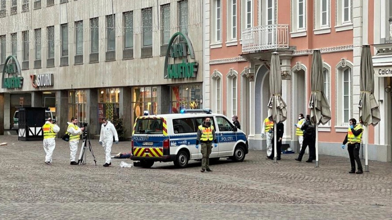 Police officers are pictured at the scene of an incident in the city of Trier, Germany, Tuesday, Dec 1, 2020. German police say two people have been killed and several others injured in the southwestern German city of Trier when a car drove into a pedestrian zone. Trier police tweeted that the driver had been arrested and the vehicle impounded. (AP Photo/Sebastian Schmitz, lokalo.de)