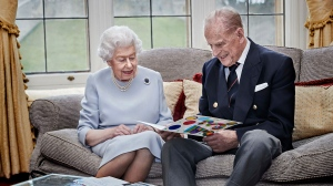 In this image released on Thursday Nov. 19, 2020, Queen Elizabeth II and Prince Philip, Duke of Edinburgh look at a homemade wedding anniversary card at Windsor Castle, England, Nov. 17, 2020, ahead of their 73rd wedding anniversary. (Chris Jackson/Pool via AP)