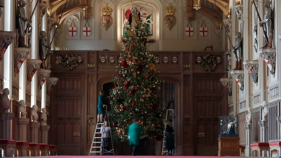 Staff from Windsor castle, adjust decorations on a Christmas tree in St George's Hall room at the castle during a media preview in Windsor, England, Friday, Nov. 29, 2019. (AP Photo/Alastair Grant)