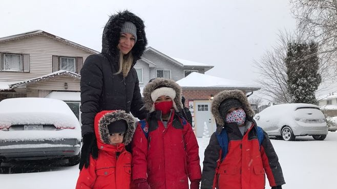 Chaza Zeatir and her children Eyad, Marwan and Ryan wait for a school bus in south London, Ont. during a significant snowfall on Tuesday, Dec. 1, 2020. (Sean Irvine / CTV News)