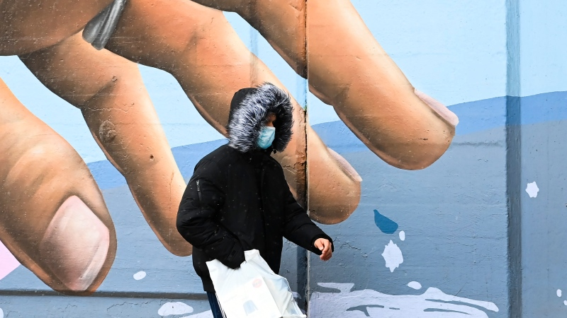 A man wearing a protective mask walks past a mural during the COVID-19 pandemic in Toronto on Tuesday, December 1, 2020. Toronto and Peel region continue to be in lockdown. THE CANADIAN PRESS/Nathan Denette