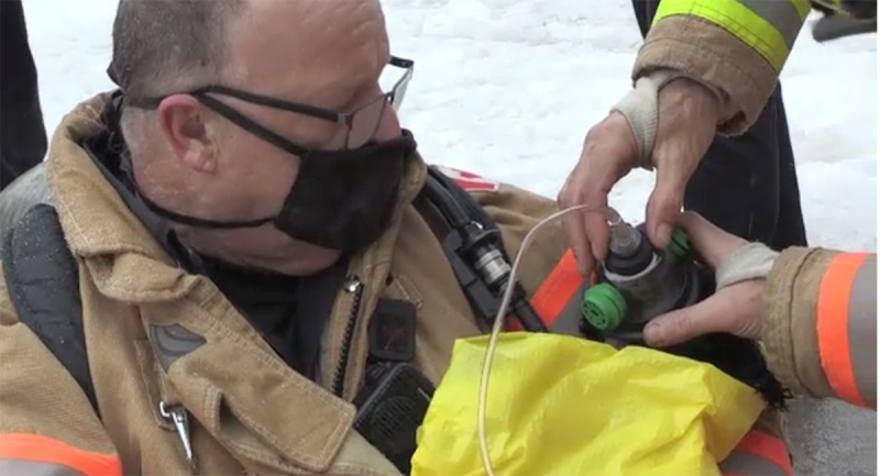 Firefighters help resuscitate a dog with oxygen after a fire in London, Ont. on Tuesday, Dec. 1, 2020. (Jim Knight / CTV News)