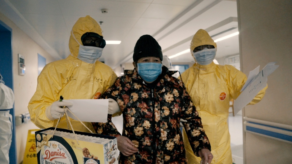 An elderly woman with COVID-19, centre, is escorted by two nurses after being admitted to a hospital in Wuhan, China in a scene from the documentary '76 Days.' (MTV Documentary Films via AP)