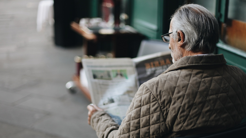 Older man reading newspaper