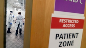 Workers talk in a hallway of a newly opened field hospital operated by Care New England to handle a surge of COVID-19 patients in Cranston, R.I, Tuesday, Dec. 1, 2020. (AP Photo/David Goldman)
