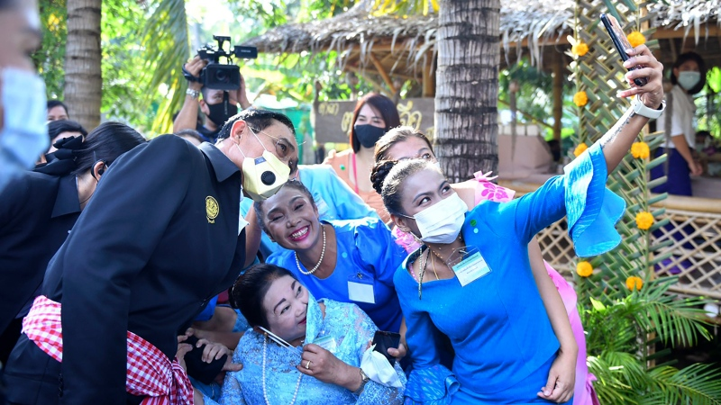 In this photo released by Government Spokesman Office, Thailand's Prime Minister Prayuth Chan-ocha, left, poses with well-wishers for a selfie in Samut Songkhram province, Thailand, Wednesday, Dec. 2, 2020. (Government Spokesman Office via AP)