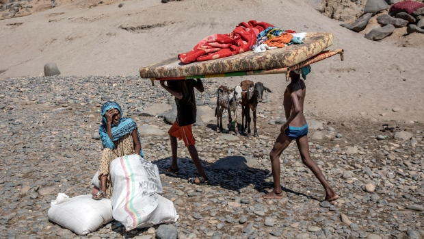 Tigray refugees who fled the conflict in the Ethiopia's Tigray carry their furniture on the banks of the Tekeze River on the Sudan-Ethiopia border, in Hamdayet, eastern Sudan, Tuesday, Dec. 1, 2020. (AP Photo/Nariman El-Mofty)