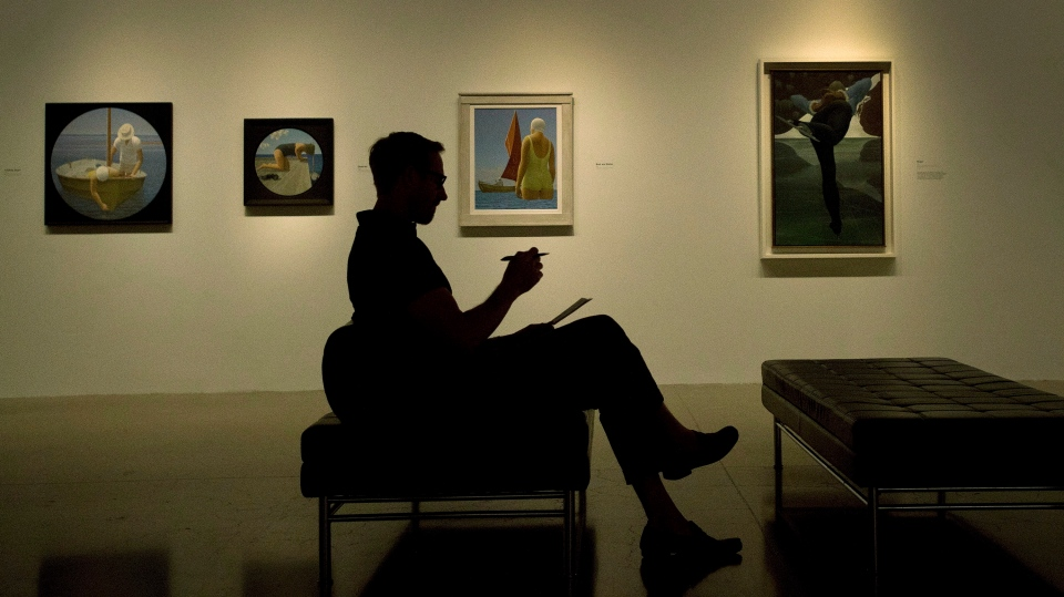 A person overlooks the art of Alex Colville during a media preview of the largest exhibition of the late Canadian painter's work ever assembled, at The Art Gallery of Ontario in Toronto on Tuesday, August 19, 2014. (THE CANADIAN PRESS/Nathan Denette)