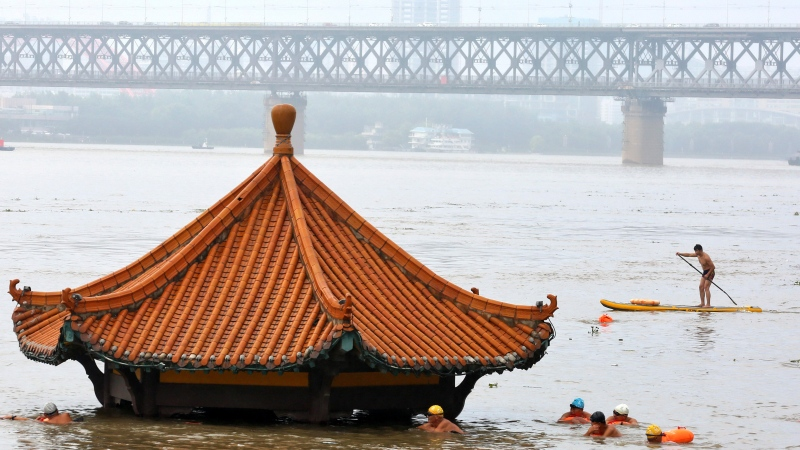 In this Wednesday, July 8, 2020 file photo, residents swim to a riverside pavilion submerged by the flooded Yangtze River in Wuhan in central China's Hubei province. (Chinatopix via AP)