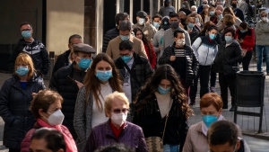 People wearing face masks to prevent the spread of the coronavirus queue up waiting their turn to buy lottery in downtown Barcelona, Spain, Wednesday, Dec. 2, 2020. (AP Photo/Emilio Morenatti)