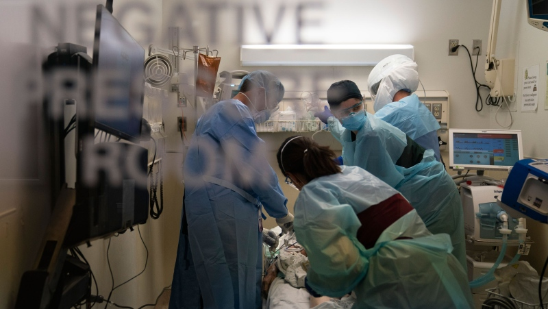 In this November 19, 2020, file photo, EMT Giselle Dorgalli, second from right, looks at a monitor while performing chest compression on a patient who tested positive for coronavirus in the emergency room at Providence Holy Cross Medical Center in the Mission Hills section of Los Angeles. (Jae C. Hong/AP)