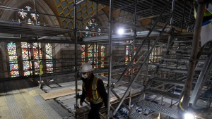 Stain glass windows are one of the few original pieces which have not been removed as a worker climbs scaffolding stairs in the Chamber of the House of Commons during a tour of the Centre block renovations Wednesday December 2, 2020 in Ottawa. THE CANADIAN PRESS/Adrian Wyld