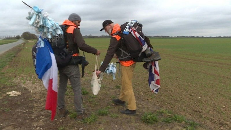Environmental activists Frederic Munsch (L) and Edmund Platt (R) bag trash, including coronavirus masks, along the TGV train route from Marseille to Paris. (AFP)