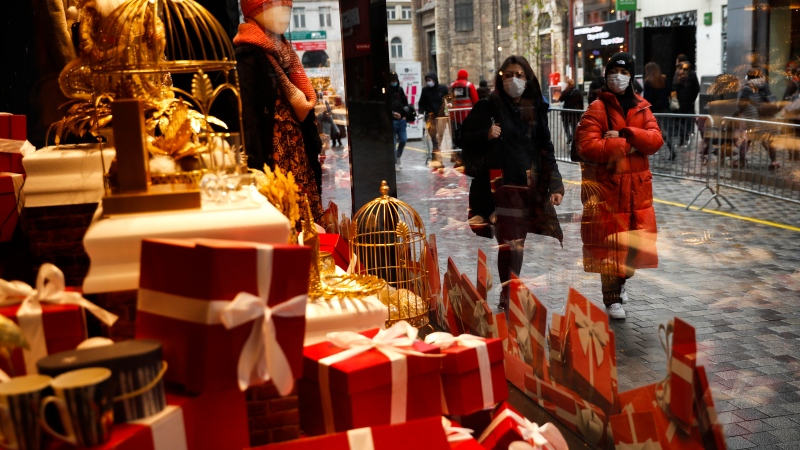 People, wearing face masks to prevent the spread of the coronavirus, walk past a display windows of a shopping mall in a commercial street in downtown Brussels, Tuesday, Dec. 1, 2020. (AP Photo/Francisco Seco)