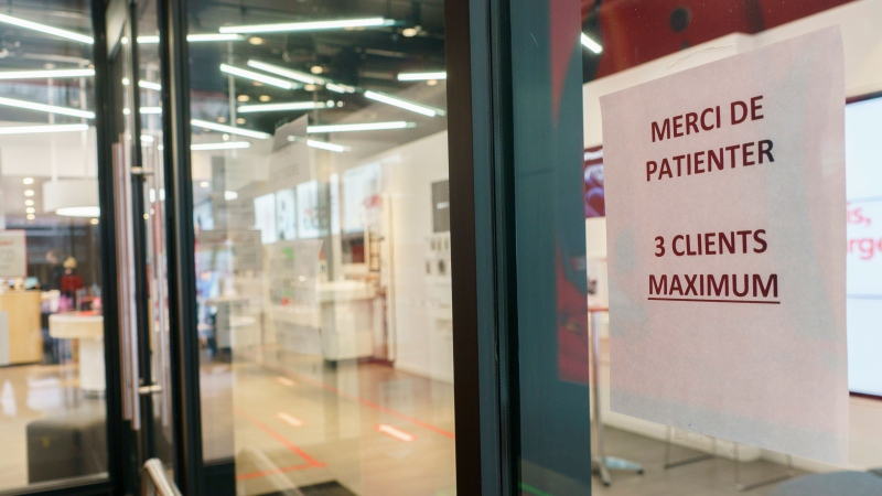 A sign showing the maximum number of clients is seen at the entrance of a phone shop in Montreal, on Wednesday, December 2, 2020. The Quebec government announced that stores will have to set the maximum capacity of customers based on floor space available to customers. THE CANADIAN PRESS/Paul Chiasson