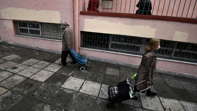 Two people wearing face masks against the spread of the coronavirus, pull their shopping trolleys outside a school during the lockdown to contain the spread of COVID-19 in the northern city of Thessaloniki, Greece, Tuesday, Nov. 3, 2020. (AP Photo/Giannis Papanikos)