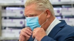 Ontario Premier Doug Ford puts his mask back on during the daily briefing at Humber River Hospital in Toronto on Tuesday November 24, 2020. THE CANADIAN PRESS/Frank Gunn