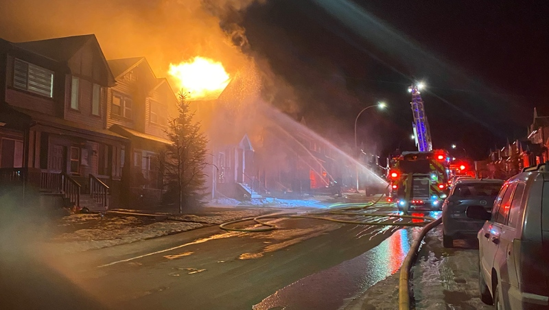 Firefighters douse homes on Nolafield Lane N.W. with water during Thursday morning's fire that spread to multiple homes (image courtesy: Khushwant Parmar )