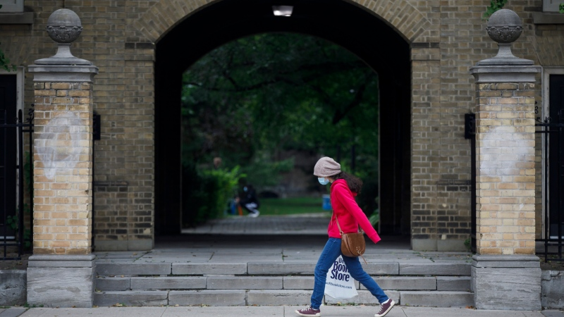 A person carrying a University of Toronto Book Store shopping bag walks on the University of Toronto campus in Toronto, Tuesday, Sept. 8, 2020, as some students in Ontario start their school year today with orientation classes. (Cole Burston/The Canadian Press)