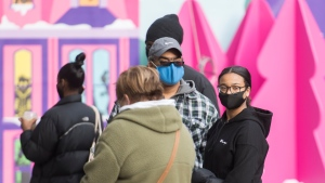 People wear face masks as they wait to enter a store in Montreal, Sunday, November 29, 2020, as the COVID-19 pandemic continues in Canada and around the world. THE CANADIAN PRESS/Graham Hughes