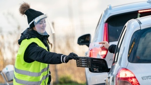 A woman wearing a face shield is handed a COVID-19 self-test at a sampling site in a car park at Svågertorp station in Malmö, Sweden, Friday, Nov. 27, 2020. (Johan Nilsson/TT via AP)