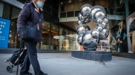 A woman wearing a mask walks past a sculpture in Calgary, Alta., Wednesday, Dec. 2, 2020, amid a worldwide COVID-19 pandemic. THE CANADIAN PRESS/Jeff McIntosh