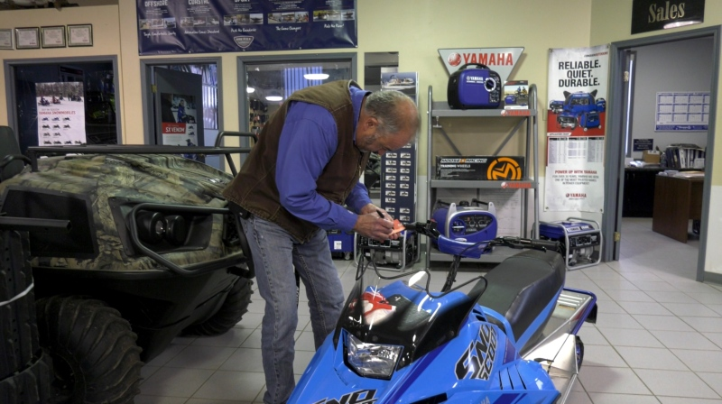 Terry Skulmoski marks this snowmobile as sold at Tru North Auto, RV & Marine Sales in Prince Albert. (Lisa Risom/CTV Prince Albert)