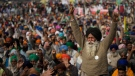 An elderly farmer shouts slogans as others listen to a speaker as they block a major highway during a protest to abolish new farming laws they say will result in exploitation by corporations, eventually rendering them landless, at the Delhi-Haryana state border, India, Tuesday, Dec. 1, 2020. (AP Photo/Altaf Qadri)