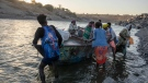 Tigray refugees arrive on the banks of the Tekeze River on the Sudan-Ethiopia border, in Hamdayet, eastern Sudan, Wednesday, Dec. 2, 2020. (AP Photo/Nariman El-Mofty)
