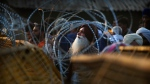 An Indian farmer looks through the barbed wire put up by the police at the site of a protest on a highway at the Delhi-Haryana state border, India, on Dec.3, 2020. (Manish Swarup / AP)
